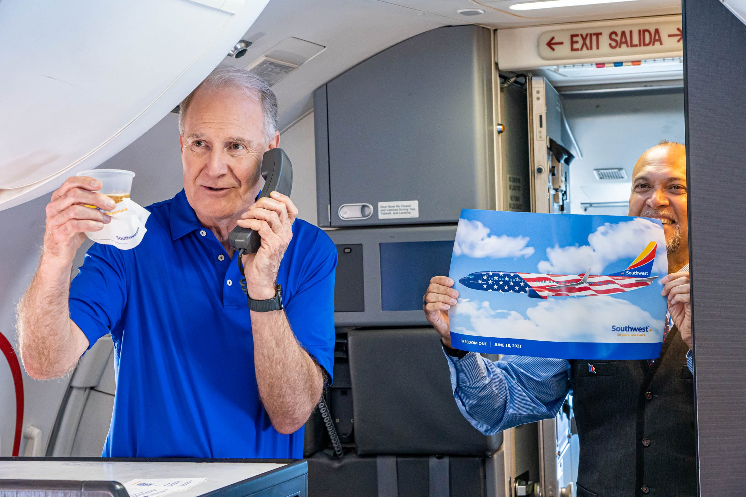 Southwest CEO Gary Kelly holds a plastic cup and speaks on aircraft public address system.